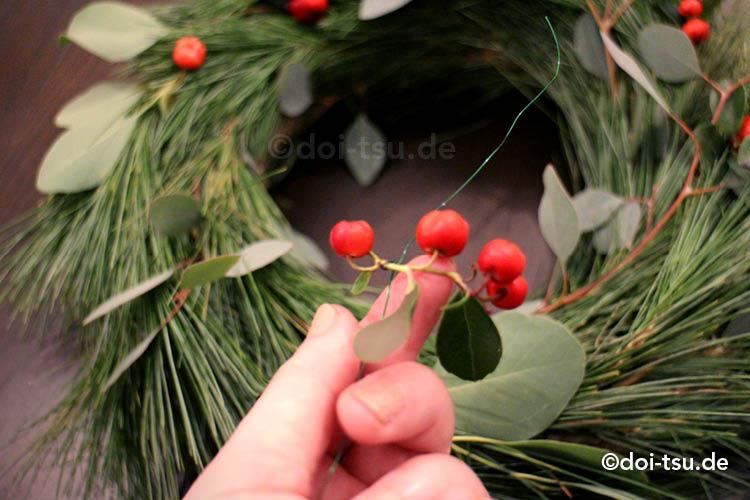 アカモノの実をクリスマスリースにワイヤーで取り付けている様子