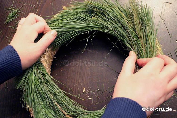 クリスマスリースをマツの葉で手作りしている様子